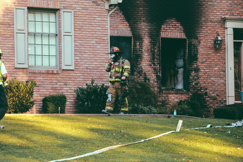 fireman walking out of house
