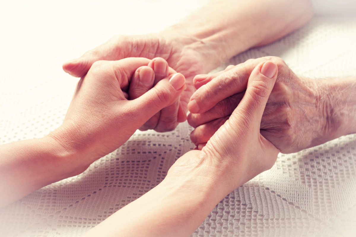 elderly hands holding onto young person hands